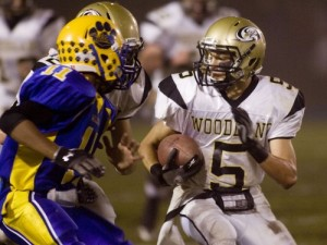 Woodland senior Brandon Fowler (5) runs behind the block of senior Tyler Slapikas on one of his long gains on the night. Fowler had three touchdowns to help lead the Hawks to a 55-32 win over Seymour Wednesday night at DeBarber Field.