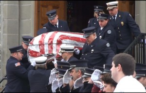 Members of Beacon Hose Company No. 1 carry the flag-draped casket of Kevin Swan out of St. Michael's Roman Catholic Church Monday. Swan had a heart attack and died while responding to a Susan Street fire last Wednesday.