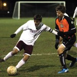 Senior Tiago Martins (7) dribbles around a Ridgefield player during Naugatuck's 1-0 loss in the second round of the Class LL state tournament last Thursday in Naugatuck.