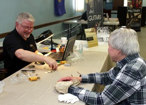 David Whisman, field buyer with the Ohio Valley Rifinery, shifts through some coins and jewlery brought in by Goshen resident Martha Tillmann Jan. 27 at the American Legion Post 17. PHOTO BY LARAINE WESCHLER.