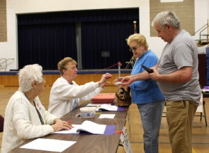 Rose Hennessey, left, and Patti Bates check in voters Paul Merriman, right, and Deanna Merriman at Laurel Ledge Elementary School in Beacon Falls on Tuesday.