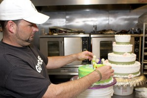 Edward Hughes, owner of Edible Dreams in Naugatuck, makes sure that a white chocolate Buzz Lightyear is sitting perfectly on one of his cakes. Hughes specializes in custom made cakes.