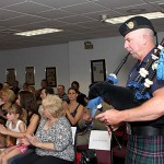 Prospect Police Officer and bagpiper John Kennelly plays to honor three officers for their work in capturing two bank robbers following a March 26 robbery at the Wells Fargo Bank in Prospect.