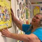 Seventh grade math teacher Louise Stack hangs a painting in her classroom at the new St. Francis - St. Hedwig school Tuesday. -LARAINE WESCHLER