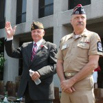 U.S. Navy veteran, longtime burgess, and Naugatuck Memorial Day parade marshal Robert Burns, left, waves to the crowd in front of Naugatuck Town Hall as Stanley Borusiewicz of the Naugatuck Veterans Council looks on.  -ELIO GUGLIOTTI