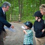 Dr. William Petit Jr., left, cuts the ribbon officially opening Michaela's Trail at the Hidden Acres Therapeutic Riding Center during a ceremony June 5. -CHRISTINE PALUF