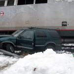 A Chevy Blazer is pinned between a fence and guard rail Thursday afternoon at the train station in Beacon Falls.-KYLE BRENNAN