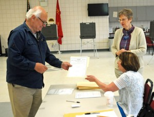Prospect resident Alexander Delelle, left, receives a ballot during a budget referendum April 29 from volunteer Kathleen Graveline, while Deputy Registrar of Voters Betty Guevin looks at the Volunteer Firehouse of Prospect. The first municipal budget proposal of $7.4 million budget failed by 66 votes and a $7.3 million budget heads to a vote Monday. –FILE PHOTO