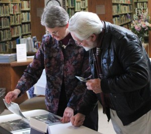 Whittemore Memorial Library Director Jocelyn Miller, left, looks over pictures documenting the rotunda restoration project with Spencer Parrish during a reception Sunday at the library to celebrate the completion of the project. –ELIO GUGLIOTTI