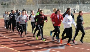 The Naugatuck High girls track team runs laps at the school during practice late last month. –LUKE MARSHALL