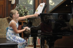 Emily Lungarini plays piano to a roomful of people last August at the Howard Whittemore Memorial Library in Naugatuck. The annual recital is a tribute to Bob Veillette, an accomplished piano player who hasn't missed the event since a stroke left him paralyzed in 2006. –RA ARCHIVE