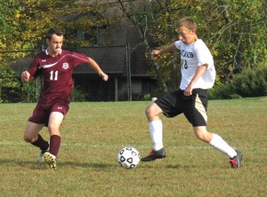 Woodland senior Adam MacDonald (18) faces off against Torrington's Seth Gesmondi (11) Oct. 8. MacDonald has made the transformation from role player to the Hawks' leader on the pitch this season. –KYLE BRENNAN