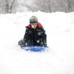 Leonardo Oliveira, Jr., 7, of Naugatuck sleds down a hill at Hop Brook Golf Course in Naugatuck Feb. 3. Students had the day off from school due to a snow storm. –LUKE MARSHALL