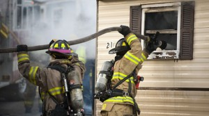 Members of the Naugatuck Fire Department and Beacon Hose Company No. 1 work at the scene of a structure fire that destroyed a house trailer and severely damaged another in a mobile home park at 129 Lewis Street in Naugatuck on Monday. –RA ARCHIVE