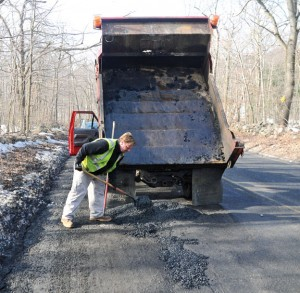 Naugatuck public works employee Jeremy Lennon fills a pothole with cold patch asphalt on Candee Road March 11. –LUKE MARSHALL