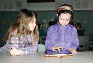 Salem Elementary School second-grader Ruby Munro looks on as second-grader Rylee Jordan works on an iPad before school March 28 during the book talk club. –LUKE MARSHALL