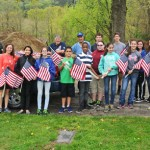 City Hill Middle School students and teachers pose for a photo with veterans Bill Matos and Manny Matos (in back on left) after helping to place American flags on the graves of veterans at St. James Cemetery in Naugatuck May 15 in preparation of Memorial Day. –LUKE MARSHALL