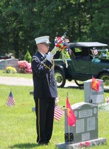 Randy Donnelly of the Volunteer Fire Department of Prospect stands at attention by the grave of a veteran in the Prospect Cemetery as Taps is played during a ceremony on Memorial Day last year. –FILE PHOTO