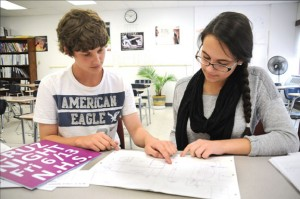 Naugatuck High School DECA members Michael Yacavone, left, and Makayla Healy look over a map of events last week for the upcoming Cruz Night fundraiser to benefit world language teacher Rebecca Cruz, who was recently diagnosed with pancreatic cancer. –LUKE MARSHALL