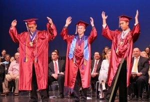 From left, Naugatuck High School Class of 2014 Valedictorian Yun Yue Chen, Class Essayist Jake Morrissey and Salutatorian Yun Chao Chen help spell out 'Naugy' for a cheer during graduation Tuesday at the Palace Theater in Waterbury. –LUKE MARSHALL