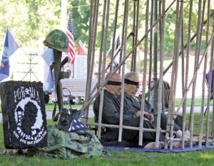 Dave Perugini, left, sits with U.S. Marine Corps veteran Mike DeVino in a bamboo cage during a POW/MIA vigil on the Naugatuck Town Green last year. –FILE PHOTO