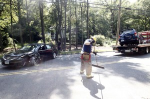 A Naugatuck firefighter sweeps up at the scene of a two-car motor vehicle collision near the intersection of Route 63 and Buckingham Street in Naugatuck on Thursday. –RA ARCHIVE