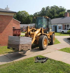 A worker transports a pallet of bricks through the courtyard at Laurel Ledge Elementary School in Beacon Falls on July 21, the first day of construction on the renovation and addition project. –ELIO GUGLIOTTI