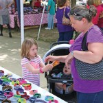 Leah Dorsey, 6, of Naugatuck puts a paracord bracelet on her mother, Amy Dorsey, Aug. 23 during the fourth annual All Arts Festival on the Naugatuck Green. –LUKE MARSHALL