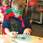 Gavin Osborne, 9, of Naugatuck designs a superhero at the Whittemore Library in Naugatuck July 23. The library handed out capes and masks for the children to wear as part of Superhero Week. The weeklong celebration, which was in honor of the 75th anniversary of the creation of Batman, included a superhero parade and screening of the 1966 Batman: The Movie. –LUKE MARSHALL