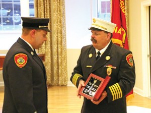 Naugatuck Fire Chief Ken Hanks, right, presents a plaque to recently retired captain James Trzaski April 8 during the fire department's awards and honor ceremony. –LUKE MARSHALL
