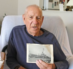 World War II veteran Jules Andes Brinchman holds up a photo of the USS Ault, a destroyer he served on from 1944 until 1946, at his home in Naugatuck. Brinchman is the grand marshal for Naugatuck's Memorial Day parade. –LUKE MARSHALL