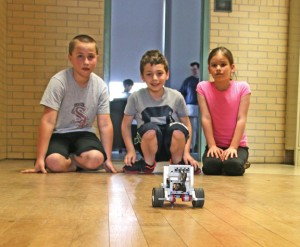 Hop Brook Elementary School fourth-graders, from left, Mikey Deitelbaum, Lucas Carrelo and Daisy Rachiele watch as a robot they built and programmed heads down a hallway of the school on May 4. The students are part of the school's newly-formed robotics club. –LUKE MARSHALL