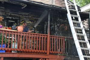 A firefighter douses the porch of the two-family house at 19 Diamond St. in Naugatuck with water following a fire Tuesday. The fire, which started in the first floor apartment, damaged both the first and second floor apartments. All the people inside escaped without injury, but five cats perished in the fire. –LUKE MARSHALL