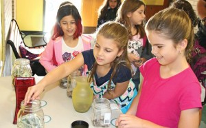 Western Elementary School third-grader Katie Umland, center, places money in a jar Sept. 18 at the school in Naugatuck while third-grader Eliviah Schroeder, left, and fourth-grader Lauren Umland look on. The school is raising money to help second-grader Olivia Thompson, 6, who is in need of a heart transplant. –LUKE MARSHALL