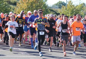 Runners take off at the start of Woodland Worldwide's Superhero(ine) Run for a Revolution last year at Woodland Regional High School in Beacon Falls. This year's run is Oct. 11. –FILE PHOTO