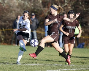 Woodland's Maribella Sousa, left, kicks the ball past Stonington's Anna Foster during the Class M quarterfinal in Beacon Falls Nov. 13. Woodland won, 4-1. -REPUBLICAN-AMERICAN