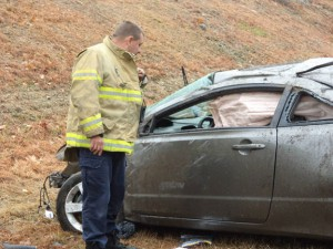 Beacon Hose Company No. 1 Fire Chief Jim Trzaski looks over the damage done to a car following an accident Wednesday on Route 8 south in Beacon Falls. –CONTRIBUTED