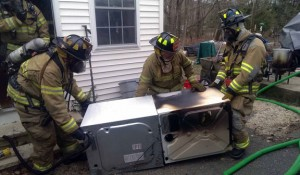 Firefighters removes a dryer that caught fire from the home at 25 Cook Lane in Beacon Falls Monday afternoon. -CONTRIBUTED