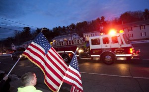 Members of Beacon Hose Company No. 1 and supporters wave American flags to welcome home U.S. Army National Guard Sgt. 1st Class Glen Francoeur as he is escorted to his Beacon Falls home on Wednesday. -REPUBLICAN-AMERICAN