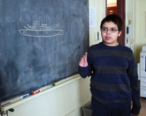Xavier Bliege, 11, and a student at Hillside Intermediate School, draws a picture of the U.S.S. Missouri in Naugatuck on Monday. Bliege has a fascination with world history, including battleships from the World War I era. Several miniature model ships that he has crafted were displayed at the Whittemore Library. -REPUBLICAN-AMERICAN