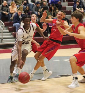 Naugatuck's Fejiro Onakpoma (35) drives the baseline past St. Paul's Austin Jones (2) and Chadd Richardson (20) Jan. 15 in Naugatuck. St. Paul won the game, 60-54. –ELIO GUGLIOTTI