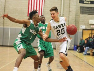 Woodland's Jon Scirpo (20) drives to the hoop past Wilby's Dimitri Yates (3) Monday night in Beacon Falls. Wilby won the game, 88-48. –ELIO GUGLIOTTI