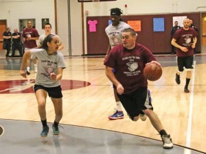 City Hill Middle School eighth-grade social studies teacher Tom Tousignant, right, drives past Naugatuck High School sophomore Alyana Sosa during the annual Clash for the Cure basketball game March 24 at Naugatuck High.–LUKE MARSHALL