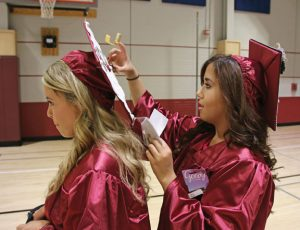 Naugatuck High School graduate Victoria Bellemare, right, puts letters on the cap of her classmate Laurel Mahler before graduation June 16 at the high school. –LUKE MARSHALL