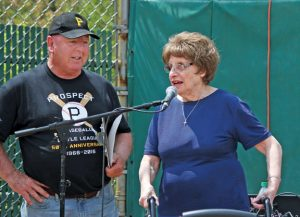 Dolores Fusco, wife of the late Leonard J. Fusco, speaks during Prospect Little League's opening day ceremony in May as league President Larry Fitzgerald looks on. The league is celebrating its 50th anniversary this year. –ELIO GUGLIOTTI