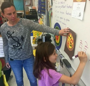 Maple Hill Elementary School teacher Jodie Burns watches as first-grader Ava Cabazas solves a math problem on the board last week. Naugatuck school officials are pleased with improved standardized test scores that they say are directly linked to changes in curriculum. –REPUBLICAN-AMERICAN