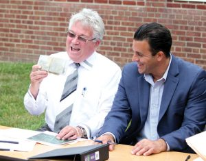 Prospect Mayor Robert Chatfield, left, laughs with Region 16 Superintendent of Schools Michael Yamin as he holds up a box of keys to Community School July 8 during a ceremony to close on the town's purchase of the school from Region 16. –ELIO GUGLIOTTI