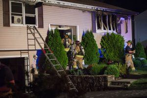 Firefighters search the damaged home at 130 Inwood Drive in Naugatuck Friday night after flames were extinguished. No one was injured in the fire. –REPUBLICAN AMERICAN
