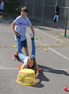 City Hill Middle School seventh-grader Yigit Yilmaz holds fellow seventh-grader Nora Lippai's legs and pushes her around as they play a live version of Hungry Hungry Hippos during a field day Sept. 16 at the school in Naugatuck. The event, which included a variety of games that require teamwork, was put on as part of the school's Wingman Program. –LUKE MARSHALL