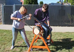 Woodland Regional High School timber team member Maddison Mircsev practices her bow saw technique as fellow timber team member Bailey Dragon holds the log in place for her during practice Oct. 11 at the school in Beacon Falls. The timber team started this fall. –LUKE MARSHALL